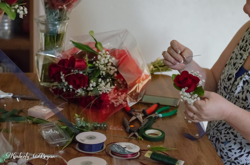 Putting together the rose boutonnieres for the wedding party.