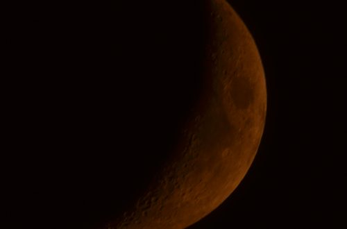 Very orange Waxing Crescent moon.