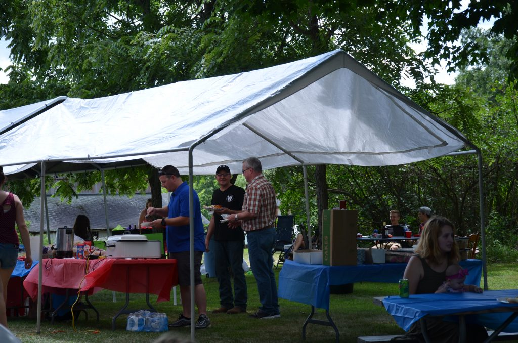 Family members gathering under the tent to eat.