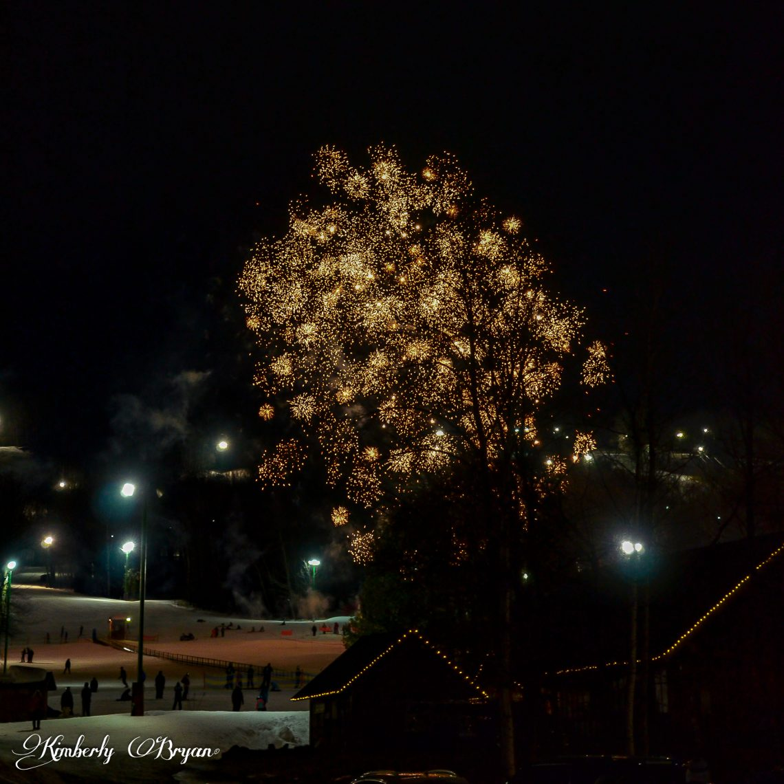 Golden fireworks exploding in the night sky at the Granite Peak Ski Hill.