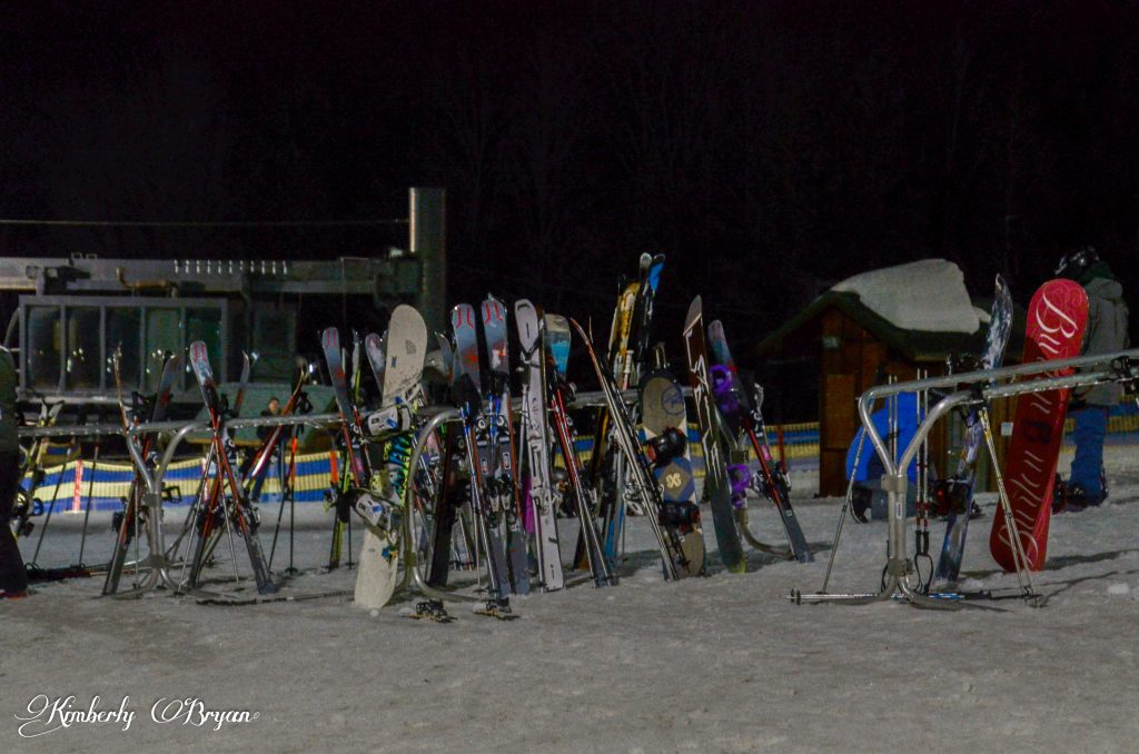 Looking at a line of Snow Boards and Skis.
