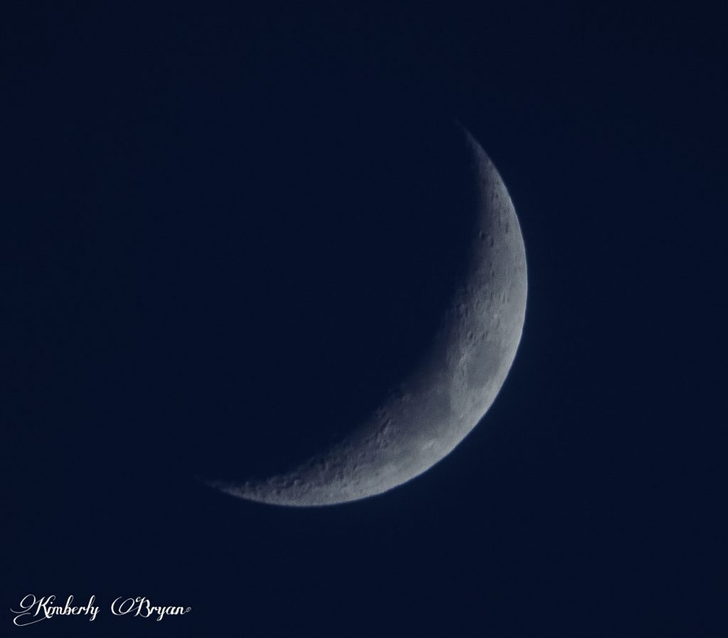 Looking at the Waxing Crescent Moon after the clouds have passed. The Moon is very blue from the atmosphere.