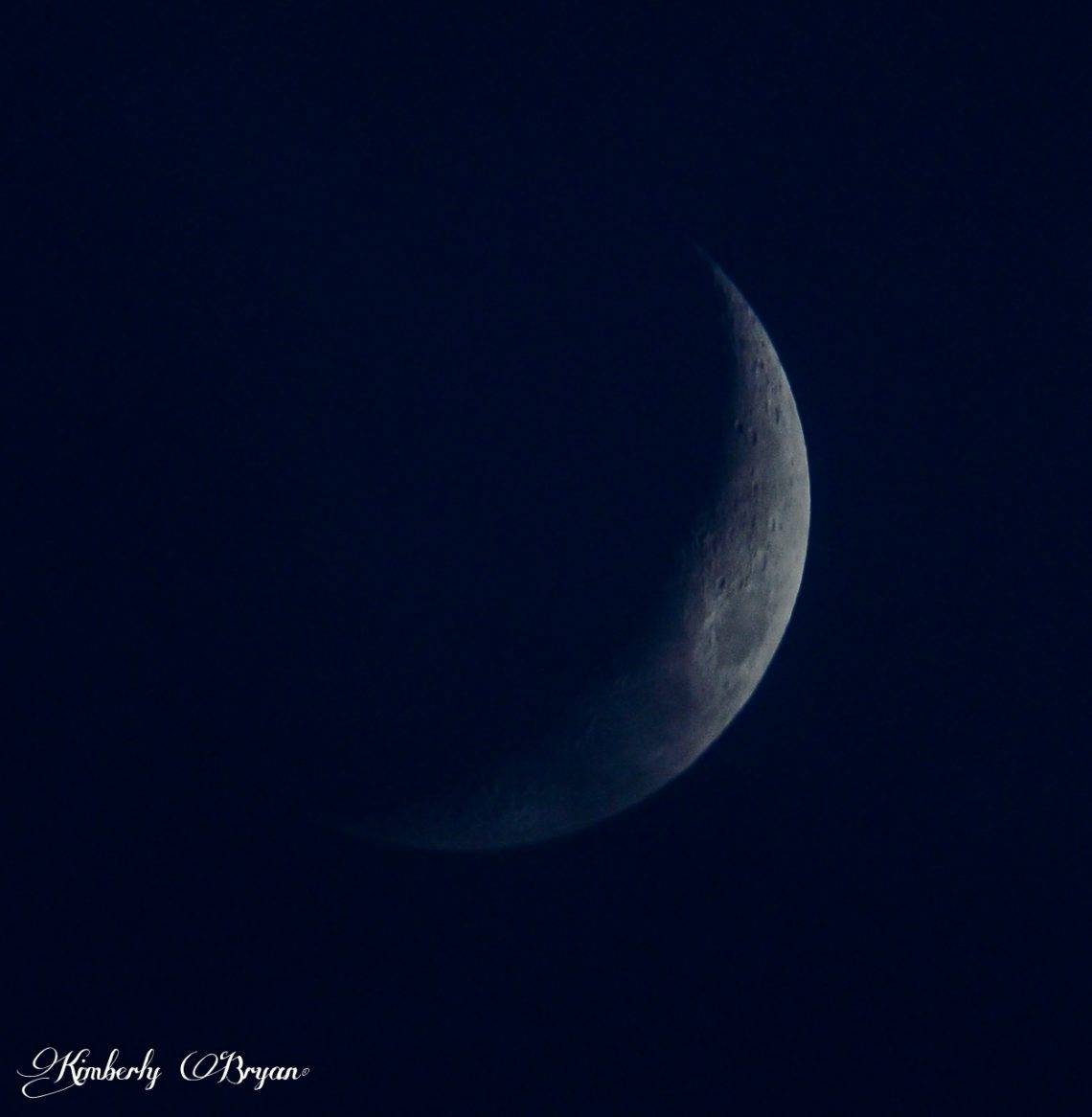Looking at the January Moon Waxing Crescent. Very thick clouds passing over the moon. Creating a very blue hue.