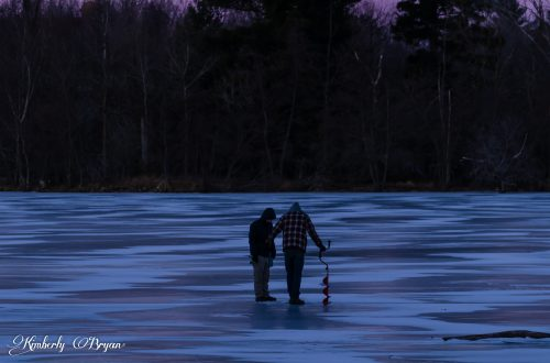 Looking out at a couple of ice fishermen making a hole through the ice.