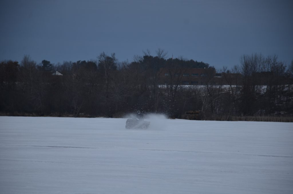 A person riding by on there 4 wheeler kicking up lots of snow, riding across the ice.