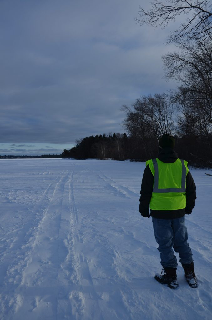 My son walking around the ice enjoying the view of the forest along the bank.