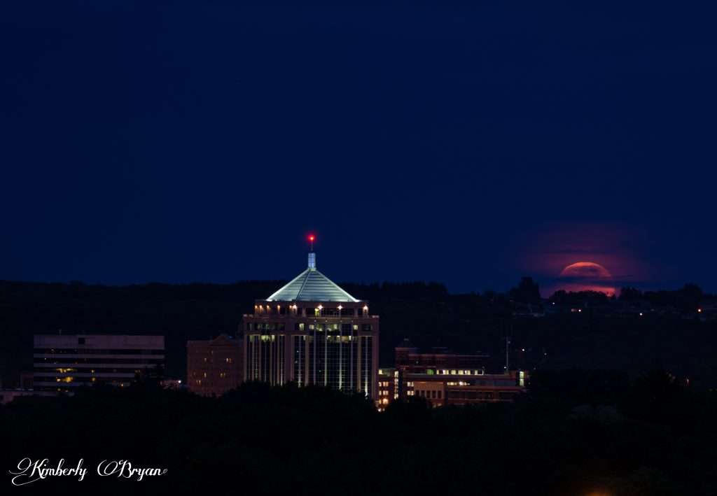 The June Strawberry moon has risen higher with some cloud cover. But the pink, orange color is coming through.