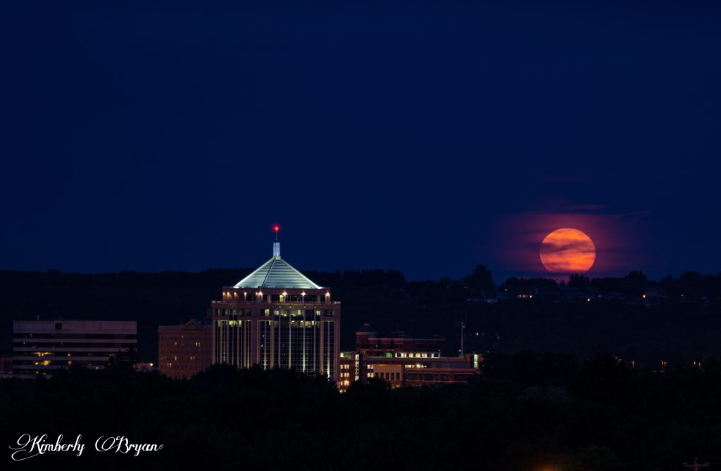 You are looking at the June Strawberry 2019 Full Moon. Rising three fourths of the way above the horizon. The clouds cleared a little so more of the bright orange, pink moon is coming through.
