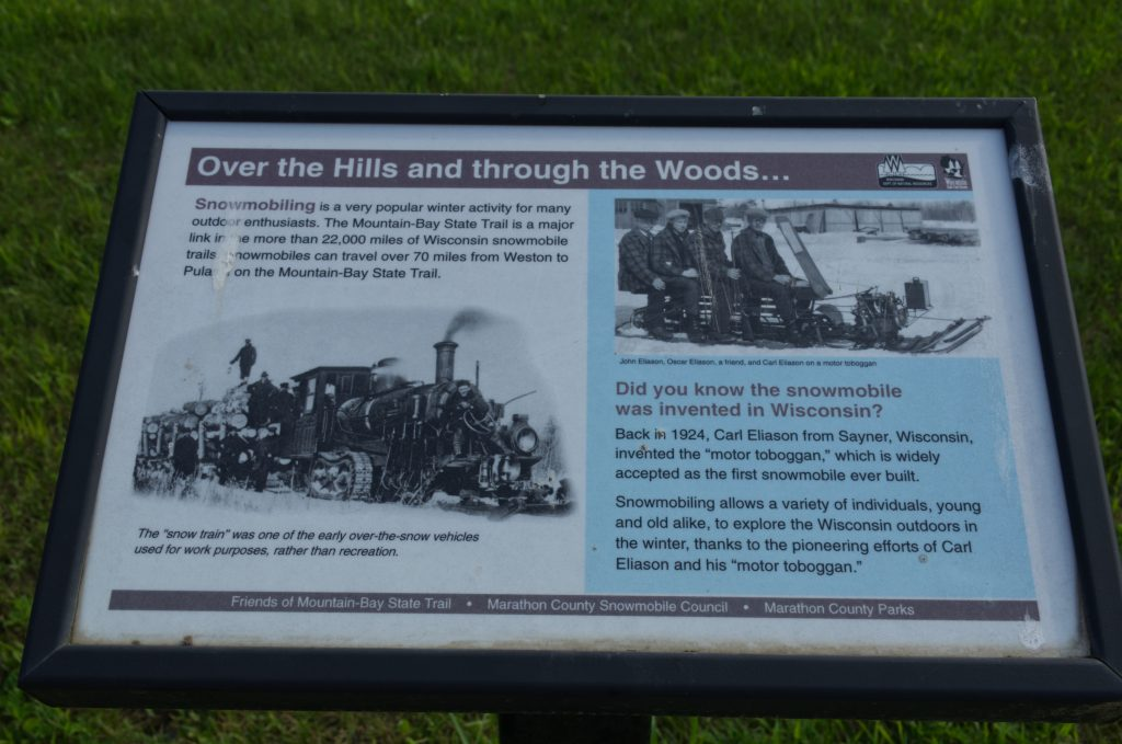 You are looking at a plaque about the first snowmobile invented in Wisconsin.