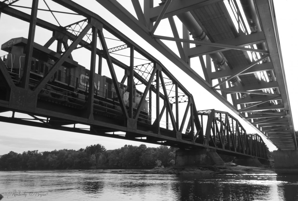 Trains, Planes and Automobiles. You are looking at a black and white photo of a train crossing over and old metal bridge. High above the Wisconsin River.