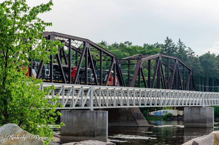 You are looking at two train engines pulling a long load of train cars, through an old metal bridge. From the Trains, Planes and Automobile post.