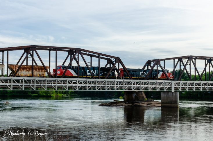 You are looking at two engines pulling a long load of trail cars. going through an old metal bridge.