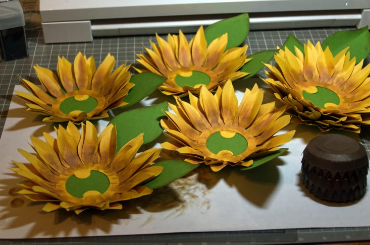 You are looking at the sunflower petals and the leaves, both inked, folded, and glued together. They are 3d and look like a real sunflower.
