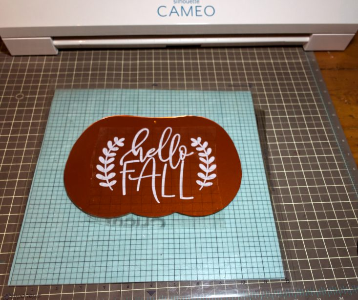 You are looking at the heat pressed vinyl on my pumpkin sign, It reads, Hello Fall. I used orange for the pumpkin and white for the phrase. This is from the post, Easy DIY Fall Hanger From The Dollar Tree.