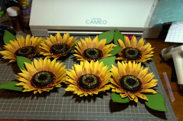 """You are looking at the completed sunflowers, all glued together and glittered. The finished sunflower is about 6.2"""" wide, 8.5"""" and two inches deep. This is from the Harvest Sunset Sunflower Wreath post."""