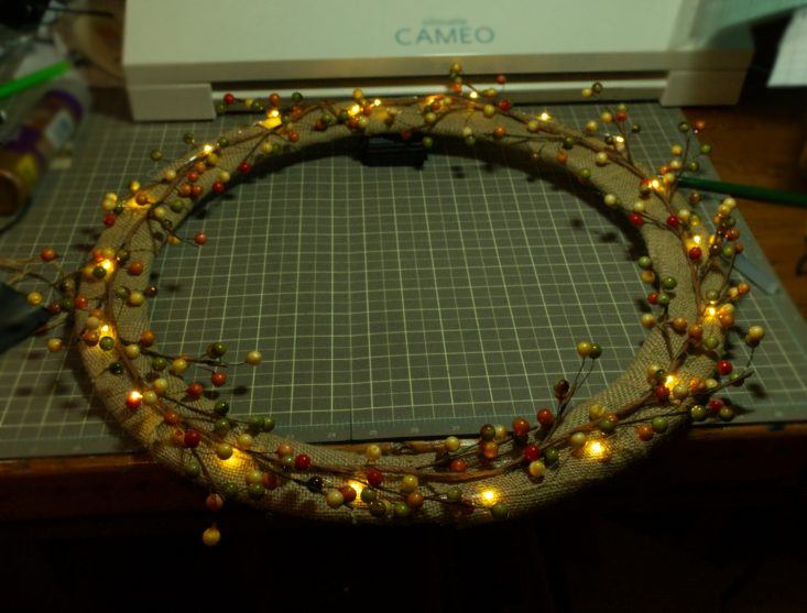 You are looking at at wreath base, that I wrapped burlap around and hot glued it in place. Then I put a berry garland around it as well. Then a string of warm battery operated LED lights.