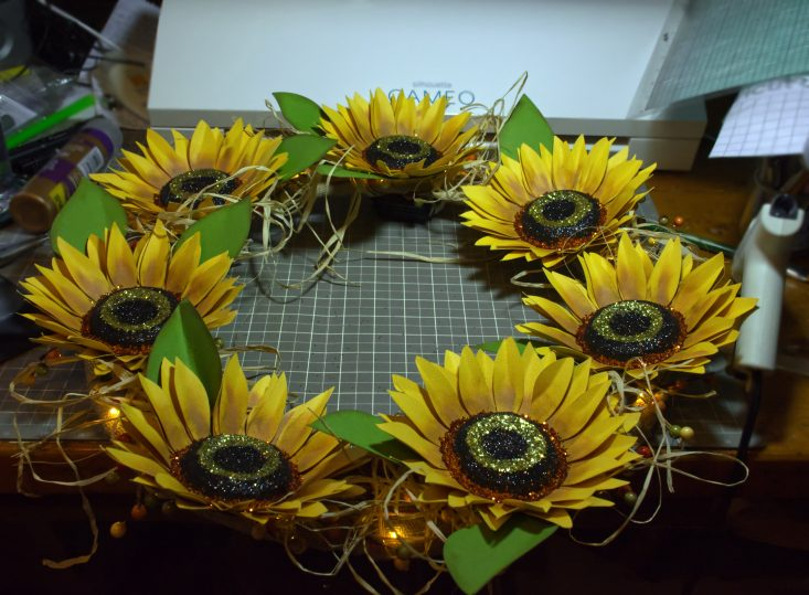 You are looking at the wreath finished with the sunflowers in place and hot glued down. I then wove natural raffia in between the flowers and garland. THis is from the Harvest Sunset Sunflower post.