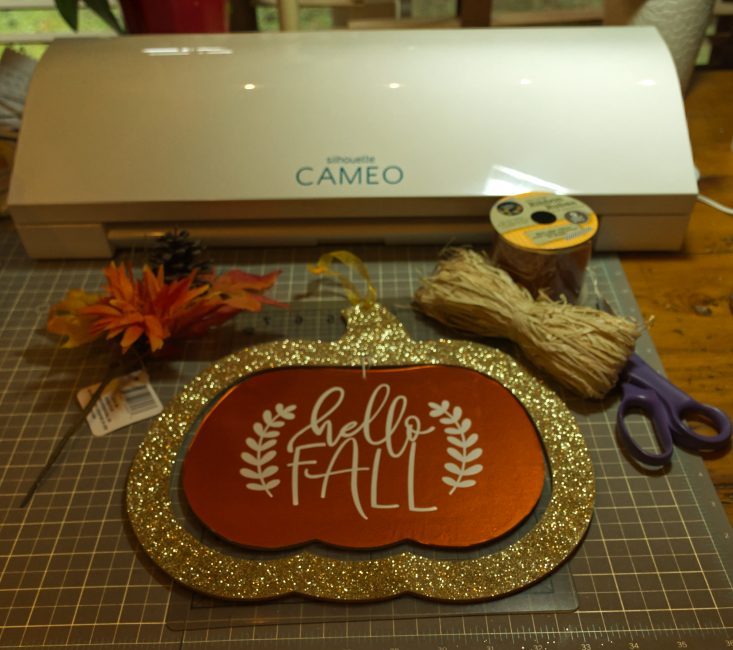 You are looking at the pumpkin sign being put back together, and I'm decorating it with raffia, leaves and an orange sunflower. All from the Dollar Tree. This is from my post, Easy DIY Fall Hanger, From The Dollar Tree.