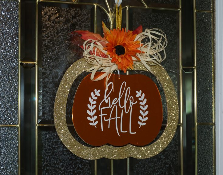 "You are looking at the completed vinyl makeover sign. That says "" Hello Fall"". I covered the sign with orange vinyl and did the phrase in white vinyl. Then decorated the top with raffia, fall leaves and an orange sunflower. This is from the post, Easy DIY Fall Hanger, From The Dollar Tree."