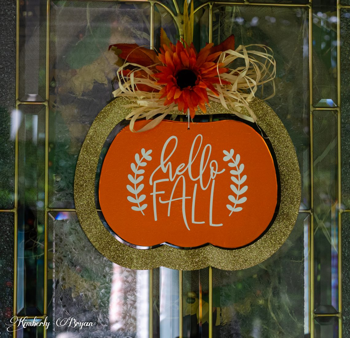 You are looking at the completed Hello Fall makeover sign. From the Easy DIY Fall Hanger: From The Dollar Tree post. It's shaped in a pumpkin with a glitter gold frame. I added natural raffia, fall leaves and an orange sunflower at the top.