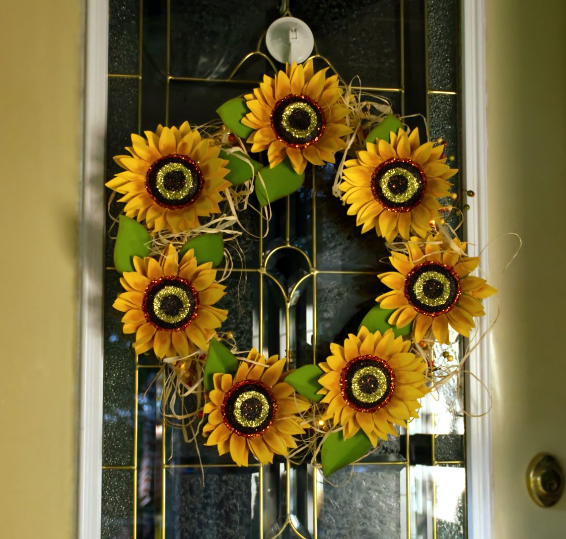 You are looking at my completed Harvest Sunset Sunflower Wreath, from my Harvest Sunset Sunflower Wreath post. The flowers are cut from paper in a bright sunflower color with glitter in the center of the 3D flowers.