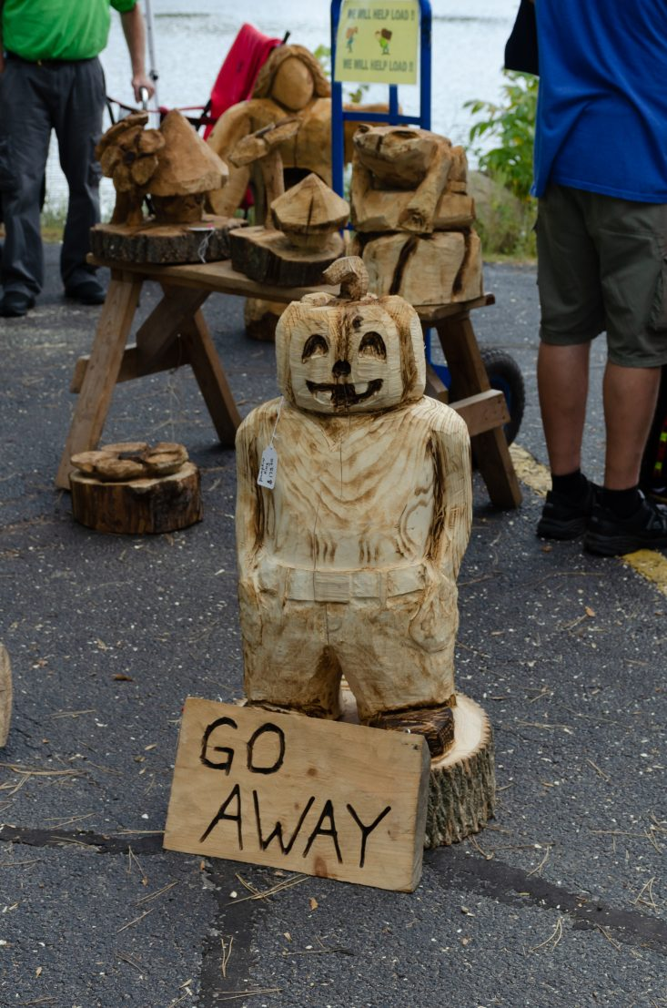 "You are looking at a pumpkin cut out from a chainsaw. It has a sign on the pumpkin that says "" go away"". This piece is for those who don't want ""trick or treaters"". This is from my post Marshfield 27th Annual Maple Fest."