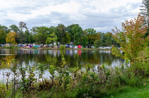 You are looking at many of the vendors from across the river from the Marshfield Maple Fest. This is a very colorful photo, all the vendor tents are reflecting in the river behind them. This is a post from Marshield 27th Annual Maple Fest.