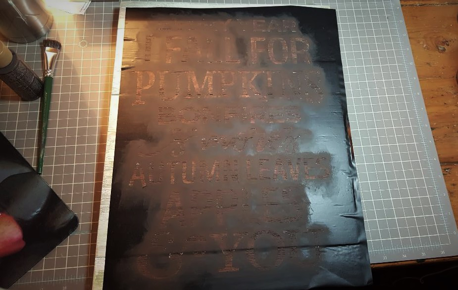 You are looking at my painted stencil, drying. I painted the phrase in burnt umber. I will let it set over night to dry before removing the stencil.