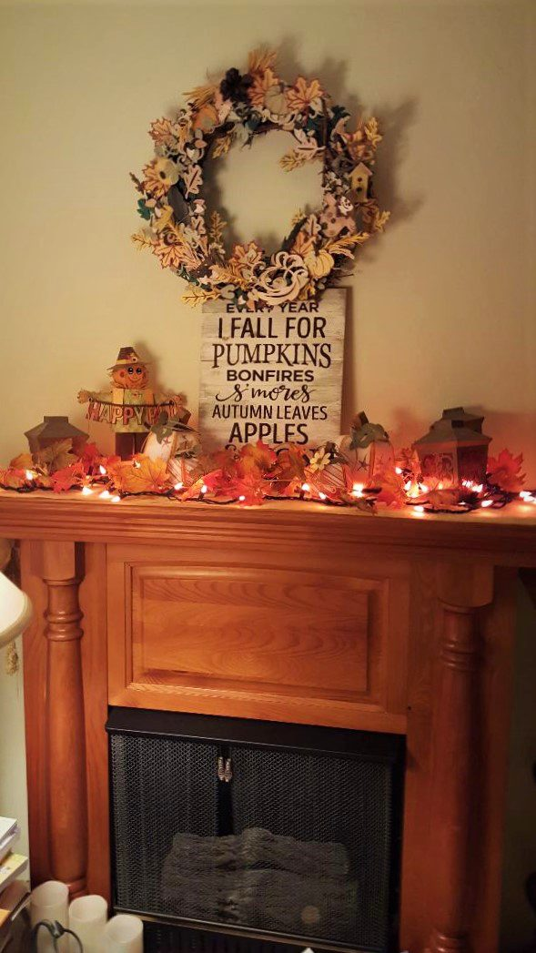 You are looking at my Fireplace Mantle all decorated for fall, with the Every Year I fall For Pumpkins Sign. As well as string of orange lights stung around paper crafted pumpkins and a scarecrow.