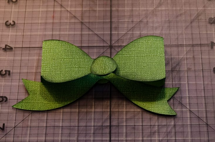 You are looking at the bow folded at it's score lines and glued together. It now has a 3d look to it and looks like a ribbon bow.