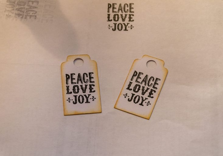 You are looking at two tags I stamped with the sentiment, peace, love, joy. I'll now glue on the base tag and attach it to the Candy Cane Christmas Card.