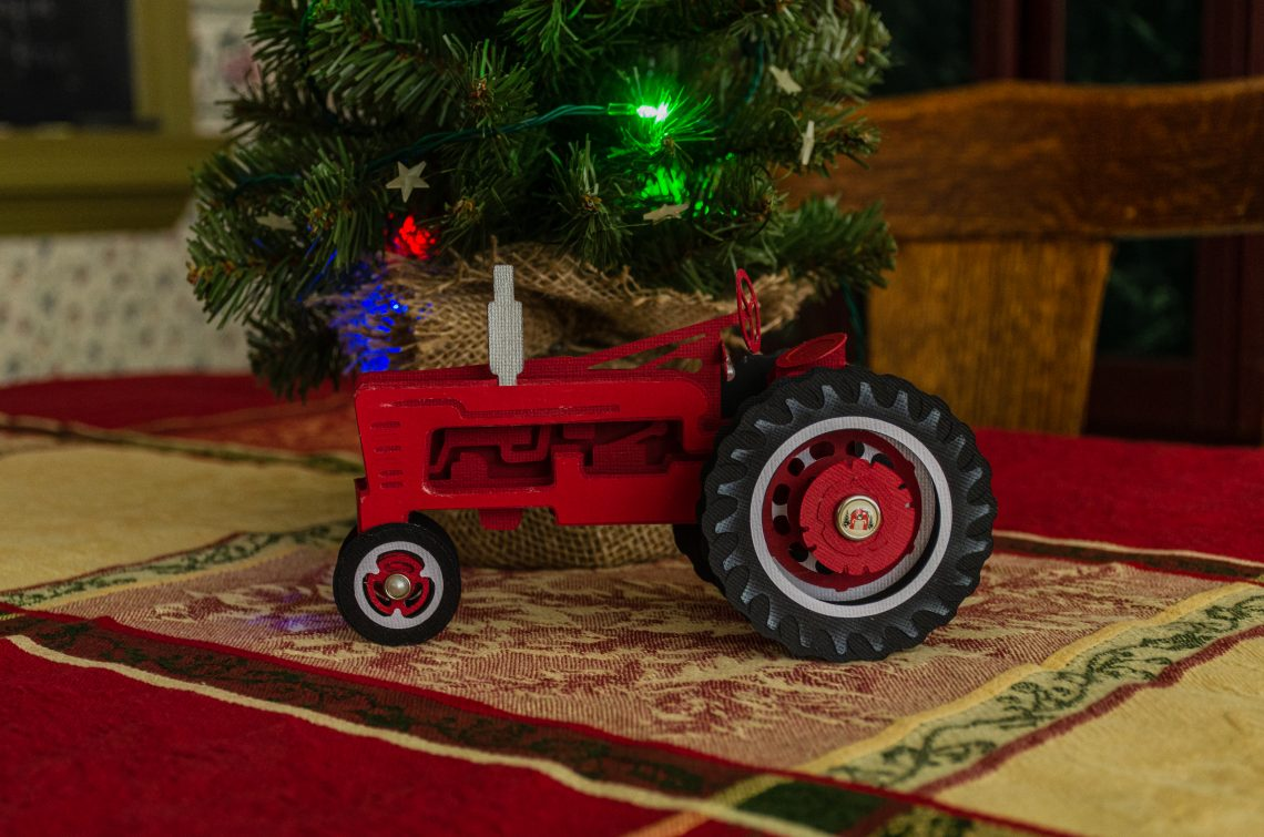You are looking the 3d Christmas Tractor Box Card. Its red with a silver smoke pipe and big tractor tires.