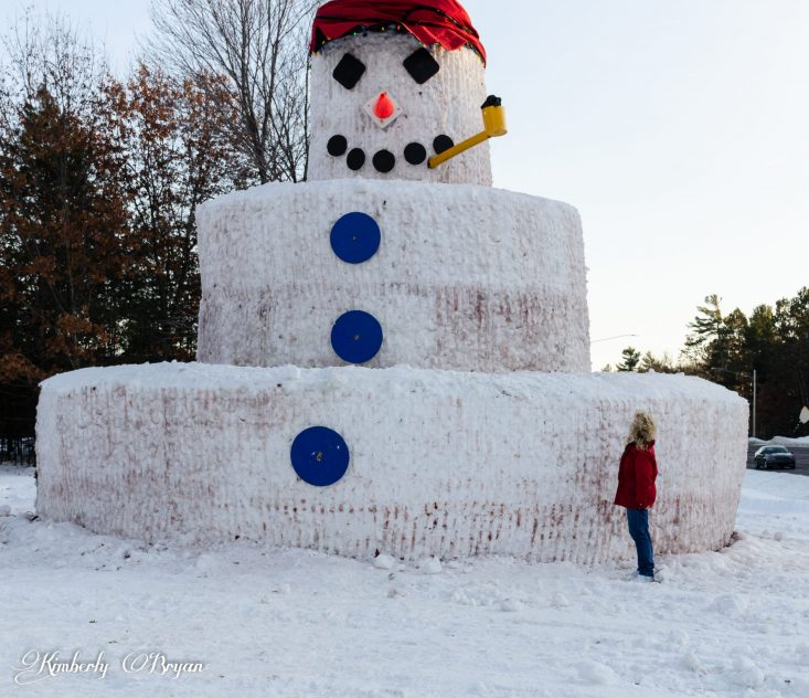 You are looking at a giant thirty foot snowman, named Snowmy Kromer. He is three tiers high with a giant hat on and a pipe in his mouth. With giant buttons and a smiling face.