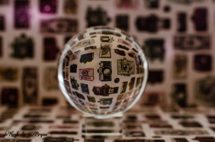 You are looking at a Lensball sitting on some scrapbook paper with old vintage cameras on it. The Lensball magnifies the reflection of the object you are looking at. In this case it's magnifying the cameras on the paper. This is from my post, Happy Valentine's Day: With a Lensball.