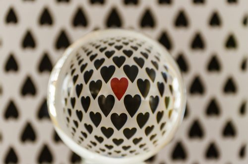 "You are looking at a Lensball in front of a sheet of card stock with hearts all over it. The Lensball gives a nice artistic reflection of the hearts. The center heart is red, while the others around it are black. This is from my post, "" Happy Valentine's Day: With a Lensball""."