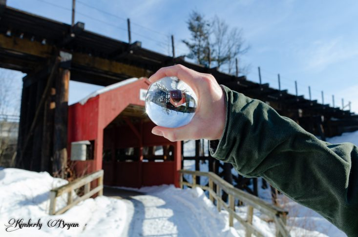You are looking at a photo of an old red covered bridge. Looking through a glass Lensball with the reflection of the old bridge.