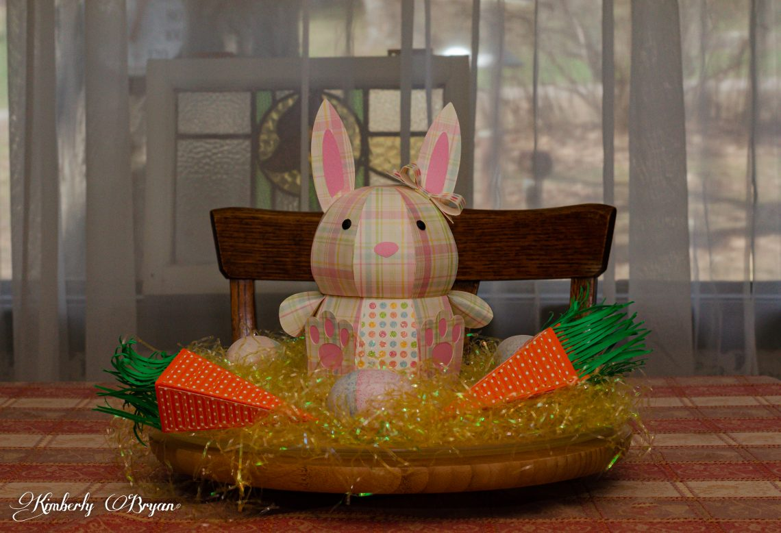 You are looking at a 3d paper bunny I put together for my Easter center piece. He is surrounded with easter grass and two 3d paper carrots with plastic eggs.