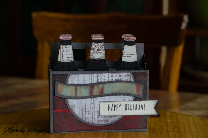 """You are looking at the completed six pack box card from the front. It reads """"Happy Birthday."""" I'm quit happy with how well this box card turned out. The designer paper I chose really made the bottles look like specialty brews. This card was very easy to assemble, I think the toughest part was choosing the right paper."""