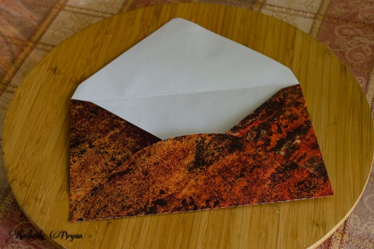 You are looking at the envelope that goes with the six pack box card. I chose a rustic marble designer paper. It's orange, black, copper and some gold.