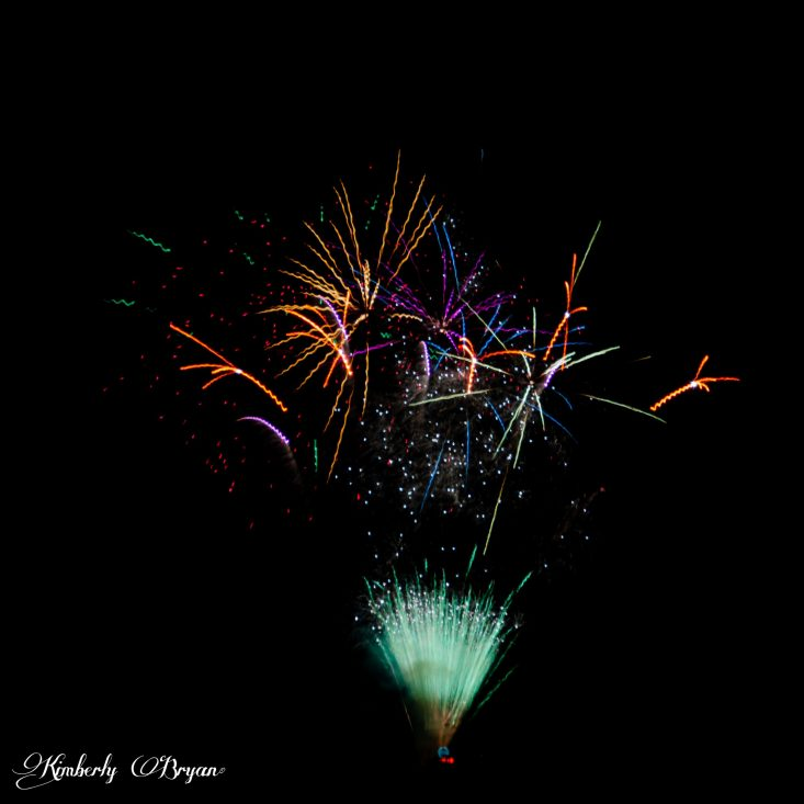 You are looking at a large unusual set of fireworks in the night sky. At it's base it looks like a fan unfolded with sparklers shooting out of it. The colors are a variety of purple, gold, teal, green, blue and white.