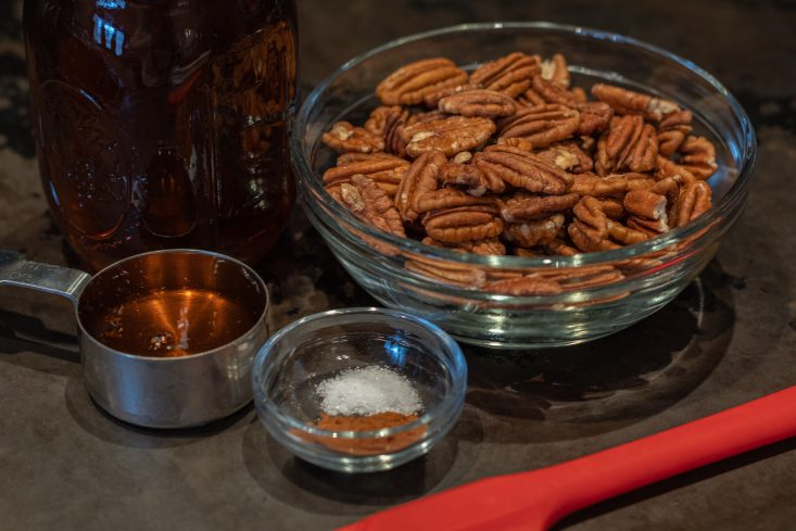 You are looking at the ingredients that I'm going to use in the Toasted pecans with real maple syrup, recipe. There's a glass bowl filled with pecan halves. a measuring cup filled with my real maple syrup. also a small glass bowl with, sea salt and cinnamon. Along with a red spatula.
