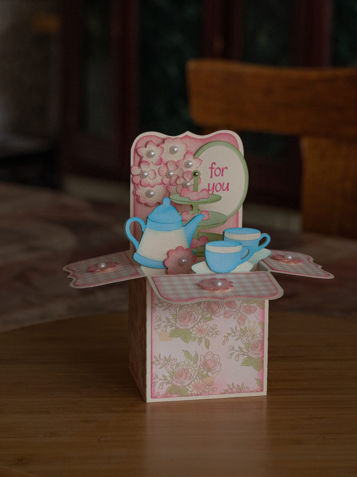 "You are looking at a box card I made called, ""It's Tea Time"". It's made with pink and cream card stock and rose designer papers. There is a 3D tea pot along with three tea cups. In baby blue and cream paper. As well as a pink vase filled with flowers and pearl centers. Also a tray with treats on it. I've embellished this card with white pearls."