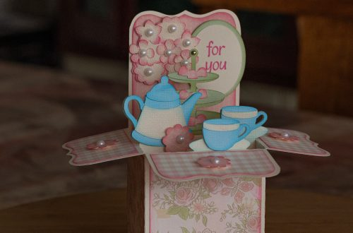 """You are looking at a box card I made called, """"It's Tea Time"""". It's made with pink and cream card stock and rose designer papers. There is a 3D tea pot along with three tea cups. In baby blue and cream paper. As well as a pink vase filled with flowers and pearl centers. Also a tray with treats on it. I've embellished this card with white pearls."""