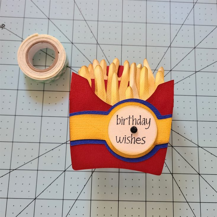 You are looking at the completed Side of Fries 3D Pop-Up Box Card. It says birthday wishes on the front of the fry box. With a cute little black gem for some extra added bling. This is such a fun and easy card to cut out and put together. Any french fry lover would really enjoy it!
