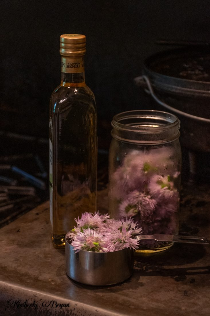 You are looking at a quart canning jar filled with freshly cut and washed chive blossoms. Also a bottle of white wine vinegar. I'm making my Chive Blossom White Wine Vinegar. I'll warm up the vinegar before pouring it into the quart jar.